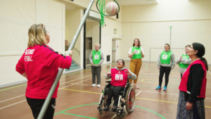 Wheelchair netball player shoots a ball through a hoop being lowered by a coach.